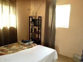 Slaapkamer met garderobe- en boekenkast en airco