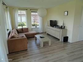 Luxe moderne grote woonkamer met openslaande deuren naar de grote tuin.