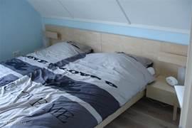 Slaapkamer met 2 ruim 2 persoonsbed hangkast en ladenkast.