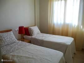 Slaapkamer met 2 eenspersoonsbedden. Ook in deze kamer een inbouwkast met hang- en leg gedeelte.