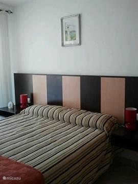 Slaapkamer 2 met 2 persoonsbed en airco en schuifdeur naar het balkon.