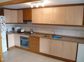 Luxe keuken met koelkast, oven, kookplaat, magnetron, vaatwasser, afzuigkap en nespresso apparaat.