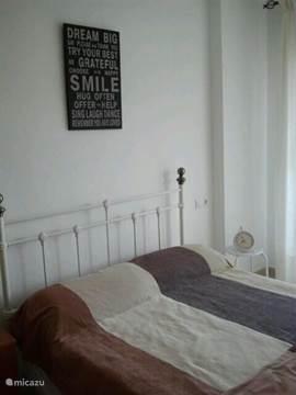 Slaapkamer 1 met 2 persoons bed en airco en schuifdeur naar het balkon.