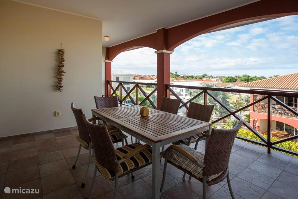 Overdekt balkon met uitzicht over de mooie tuin met zwembad.