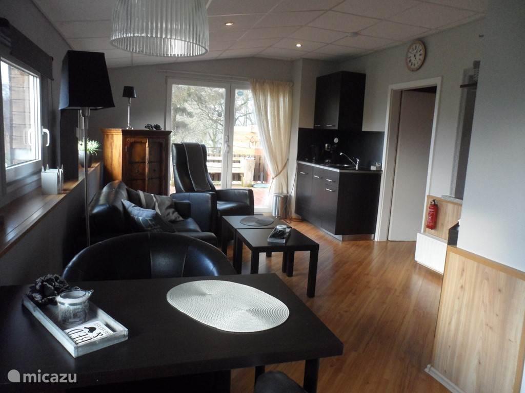Ruime woonkamer met open keuken, tuindeuren naar het terras.