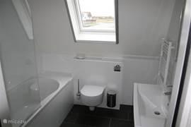 Vakantievilla Larissa in Giethoorn heeft op de verdieping een tweede badkamer met ligbad/douche, toilet en wastafel met grote, verwarmde spiegel.