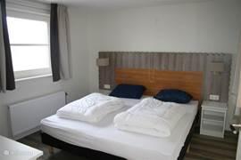 De slaapkamer beneden in Vakantievilla Larissa in Giethoorn is voorzien van 2 boxspringbedden en een flatscreen TV. Alle ramen zijn voorzien van horren.