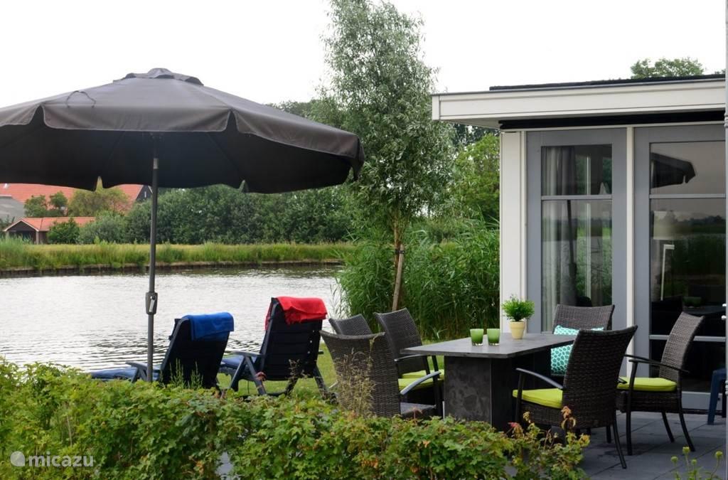 Op het terras staat een grote tafel met tuinstoelen. Op deze plek heb je volledige privacy doordat er geen buren zijn. Aan de overkant van het water loopt alleen een fietspad.