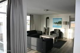 Vakantievilla Larissa in Giethoorn heeft een ruime woonkamer met een sfeervolle gashaard, flatscreen TV en openslaande deuren naar het terras. Door de grote raampartijen heb je een fantastisch vrij uitzicht over het water en de natuur van Giethoorn.