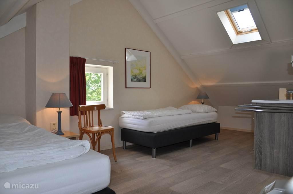 Ruime zolderkamer voor twee personen met eigen wasgelegenheid.