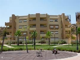 Aanzicht appartementengebouw met het penthouse rechtsboven aanpalend mediterrane tuin, park en zwembad.