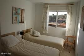 Slaapkamer 2 met 2 1-persoons bedden, 2 nachtkastjes en schuifwandkast.
