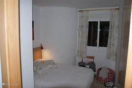 Slaapkamer 3 met een kleiner formaat 2-persoonsbed (130x200), schuifwandkast en poef.