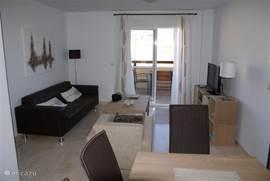 Voorzijde woonkamer met aanpalend balkon met terrastafel en 4 stoelen. Tv-Meubel met Tv, tuner en DVD-speler.