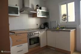 Keuken met koelkast, vrieskast, marmeren aanrechtblad, oven, keramische kookplaat, afzuigkap, magnetron en alle verdere keuken benodigdheden.