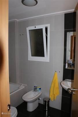 Badkamer 2 met bad met badwand (douche), wastafel, toilet en bidet.