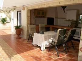 Van links naar rechts de buitendouche, toilet en buitenkeuken met zonnescherm tegen de felle zon.