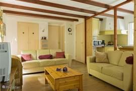 Sfeervolle woonkamer met open keuken. Achter de louvredeuren bevindt zich  de bedstede!