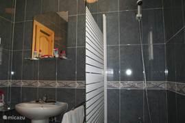 De blauwe badkamer is op de begane grond en heeft niet alleen een douche, wastafel, toilet en bidet, maar ook een ligbad.