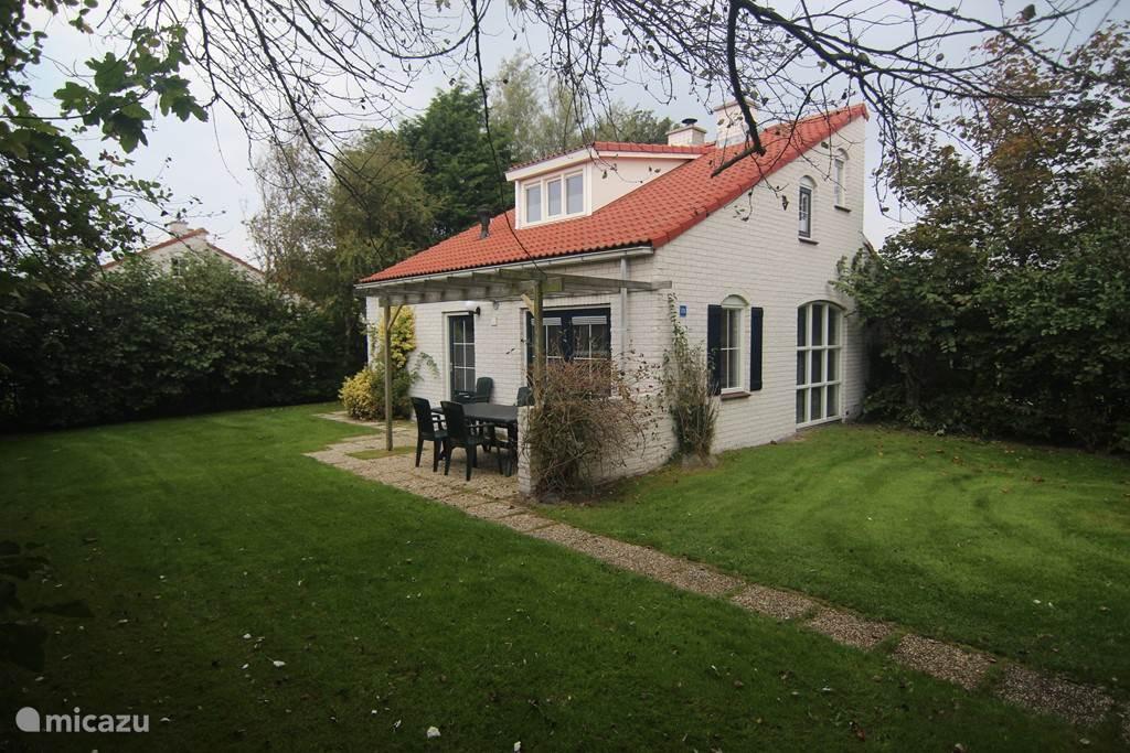 Een met openslaande deuren bereikbaar terras met tuinstoelen en tafel op het zuiden gelegen