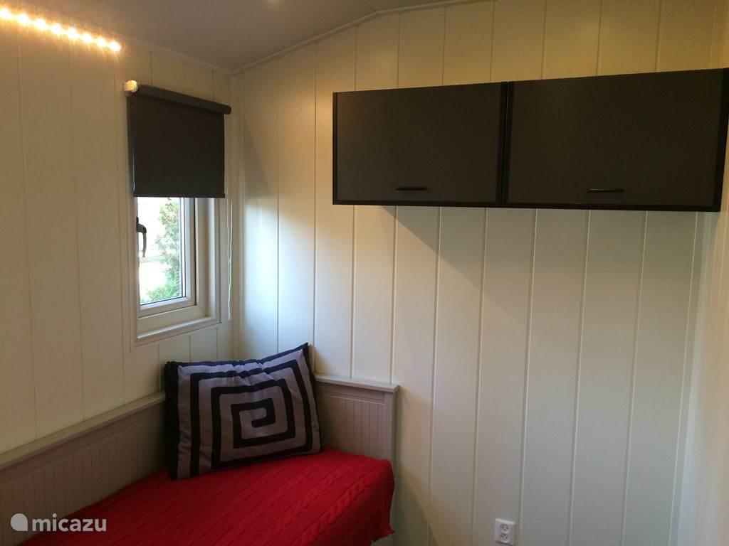 De tweede slaapkamer is voorzien van een tweepersoons uitschuifbed. Er is een campingbedje en kinderbadje aanwezig. Wanneer het bed niet uitgeschoven is, is er plaats voor het campingbedje.