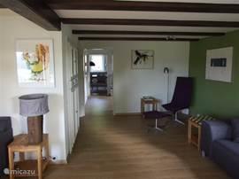 Zicht vanuit de woonkamer door de keuken naar de eetkamer. Overal in het huis hangen originele kunstwerken.