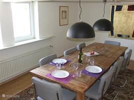 De sfeervolle eetkamer biedt plaats aan acht mensen.