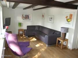 De gezellige woonkamer met tv-hoek.