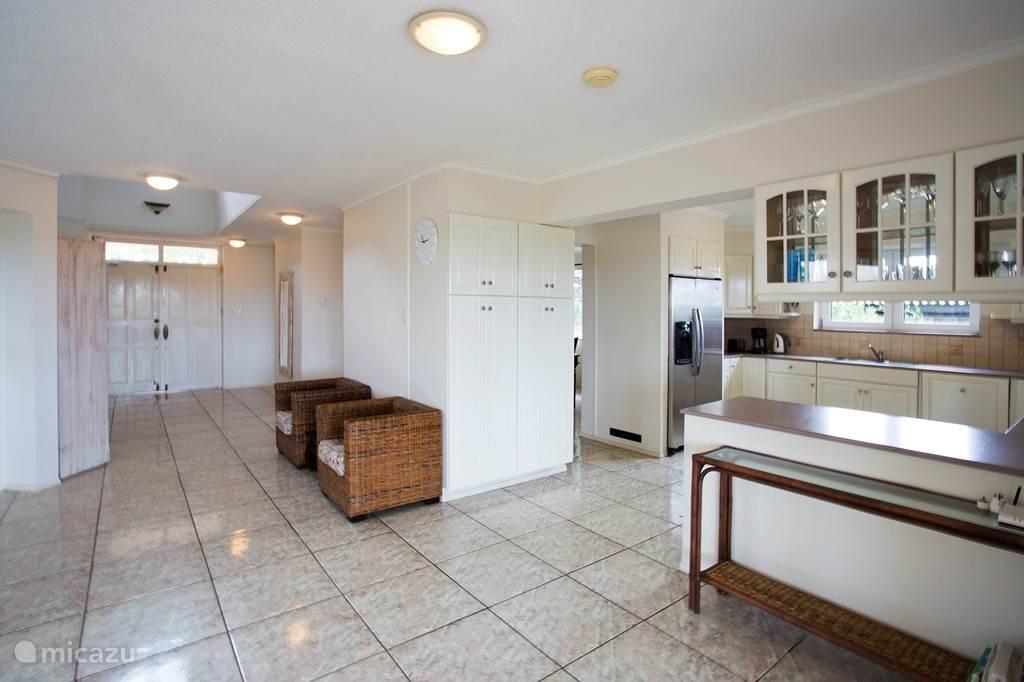 Een doorkijk naar in het woongedeelte binnen richting voordeur. Rechts de keuken.