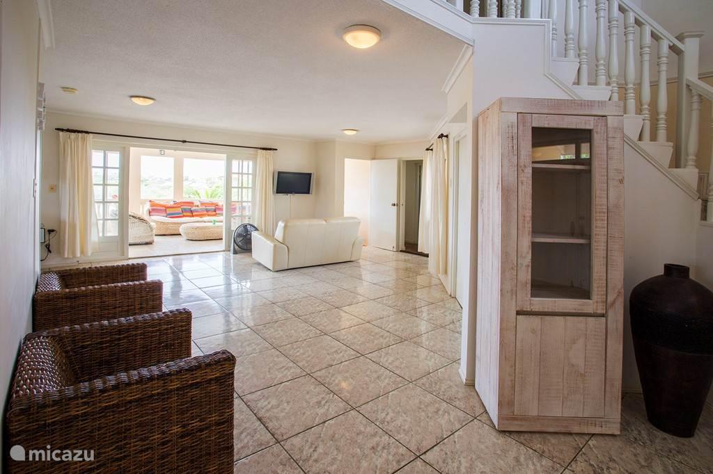 Een doorkijk naar in het woongedeelte binnen richting porch. Links de keuken, rechts achterin de trap naar het zwembad beneden.