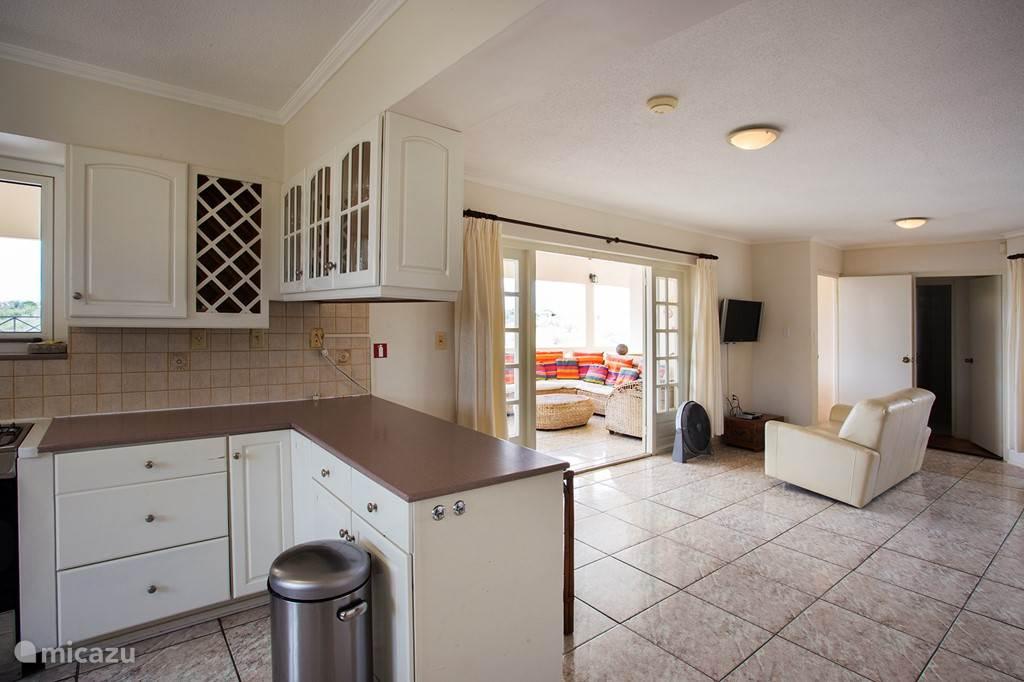 Blik van keuken naar de porch toe. Rechts de deur naar de trap van het zwembad en de slaapkamer beneden.