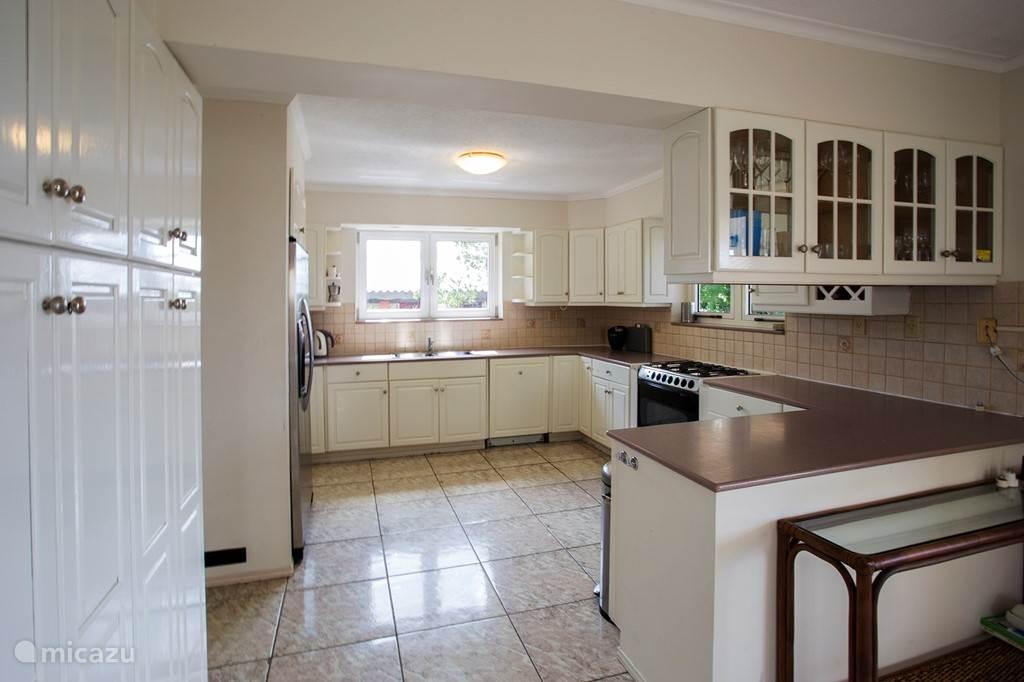 Volledig ingerichte keuken, met dubbeldeurs koelkast, 6 pits gasfornuis, oven, koffiemachine, waterkoken en broodrooster.