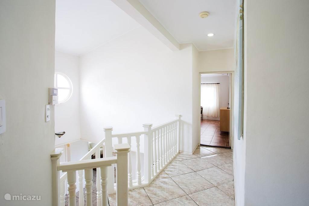 Bovenaan de trap naar links, waar de master bedroom met prive badkamer is.