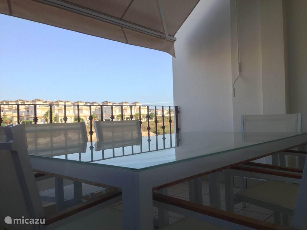 Het balkon aan de voorkant met 6 stoelen en een zonnescherm. Hier ontbijt je met de opgaande zon op het balkon; heerlijk ook in het voor- en naseizoen.