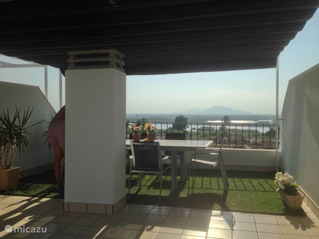 Het dakterras met zonnescherm en een prachtig uitzicht over het natuurpark, de bergen en de zonsondergang.