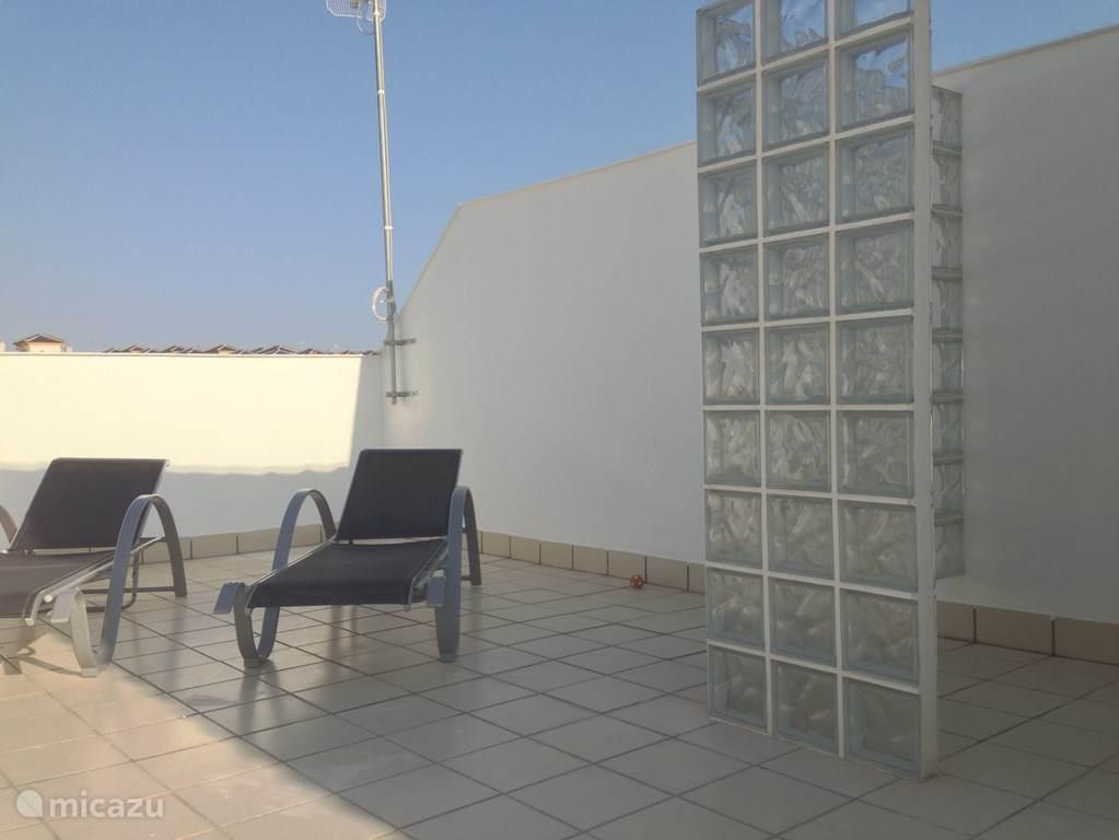 Een riante buitendouche, 2 zonnebedden, een eettafel met 6 stoelen, een vaste gemetselde barbeque en een enorm zonnescherm zijn aanwezig op het dakterras.