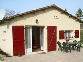De voorkant van Le Fenil, met openslaande deuren naar het terras en de boomgaard