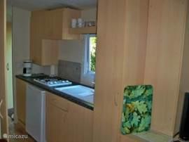 Volledig ingerichte keuken met o.a koffiezetter, koelkast met vriesvak en vierpits gasfornuis.