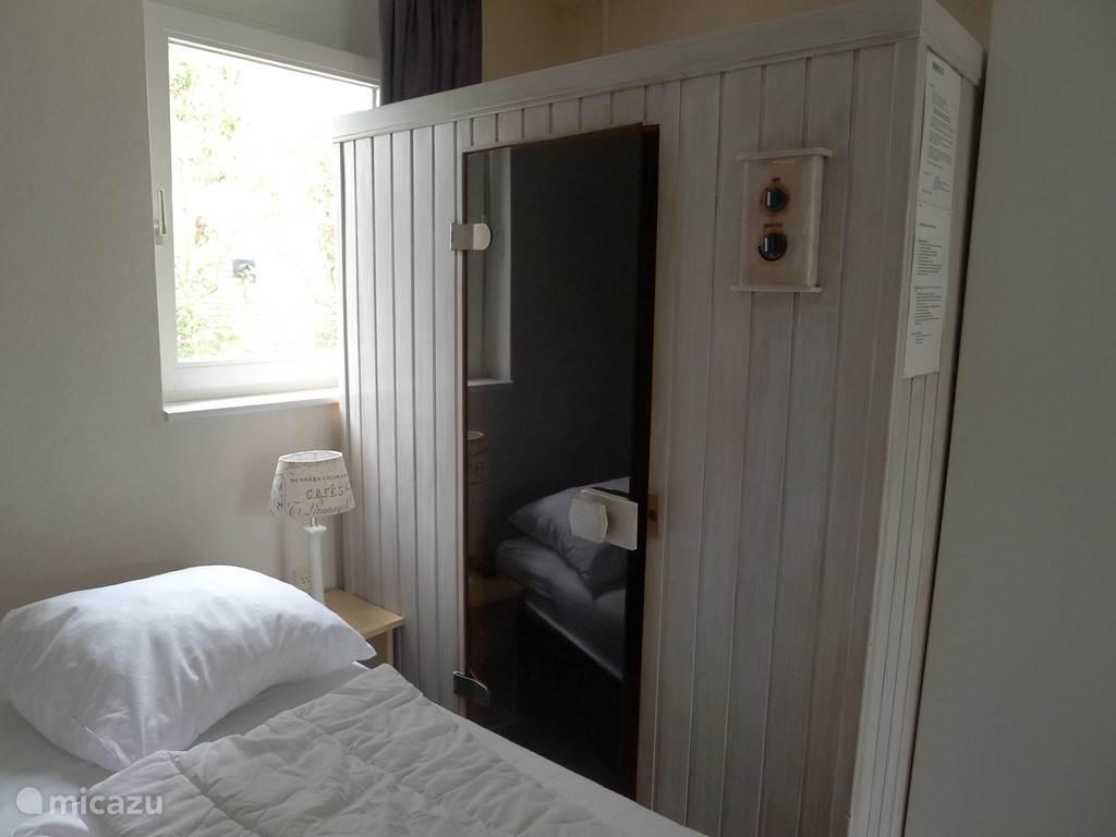 slaapkamer met infrarood sauna en aangrenzende badkamer met ligbad