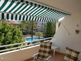 Het balkon van 3x5 meter aan de woonkamer, met uitzicht op de tuin en het zwembad.