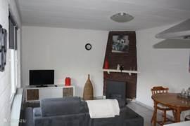 Een gezellig ingerichte woonkamer met lcd tv en gashaard.