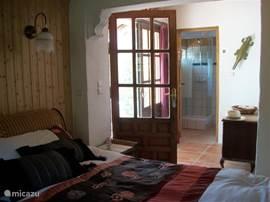 slaapkamer met badkamer met openslaande deuren en terras