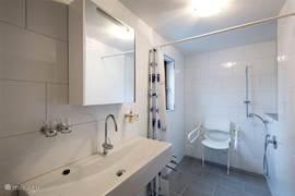 rolstoel toegankelijke badkamer met ruime douche hoek