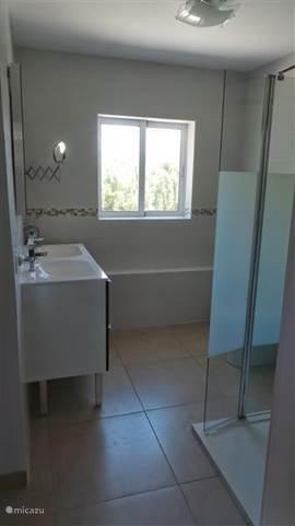 grote badkamer met dubbele wastafel en rain shower in bovenappartement
