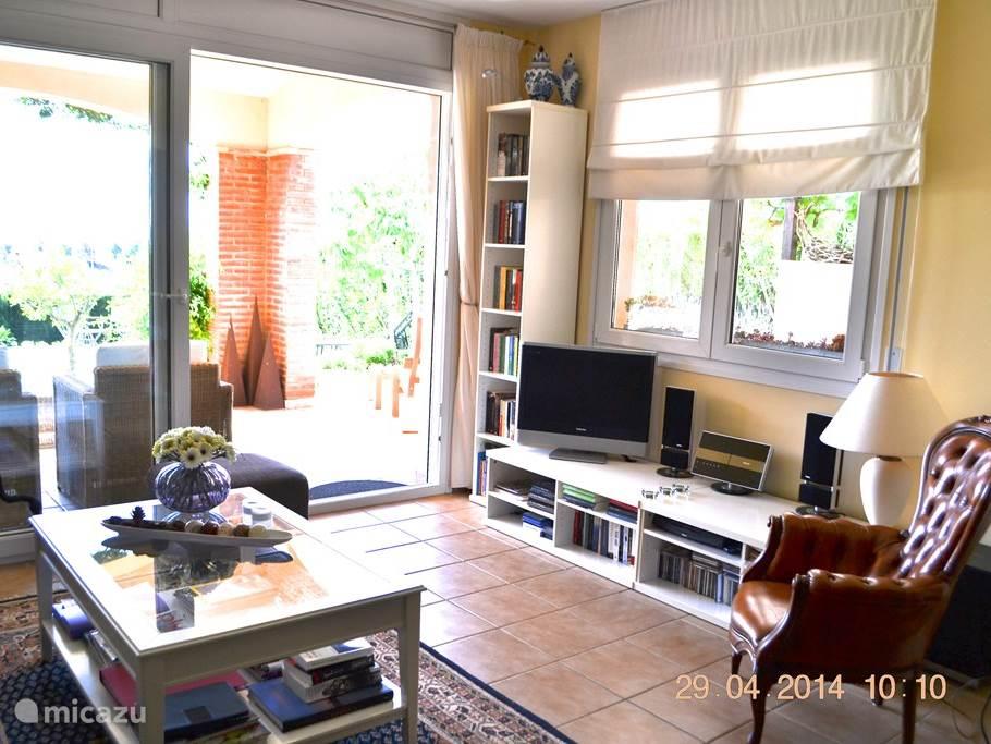 deel van zithoek in woonkamer, met tv , audio en boekenkast.