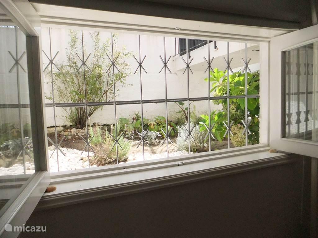 rustig uitzicht van de woonkamer naar een afgesloten sier tuin.