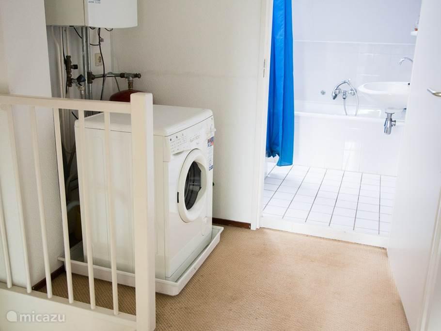 Wasmachine en badkamer met ligbad