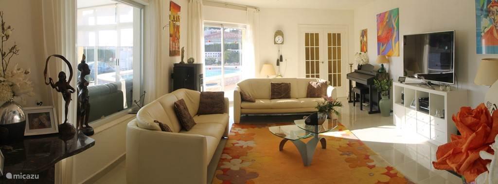 Huiskamer met grote TV en Nederlandse zenders