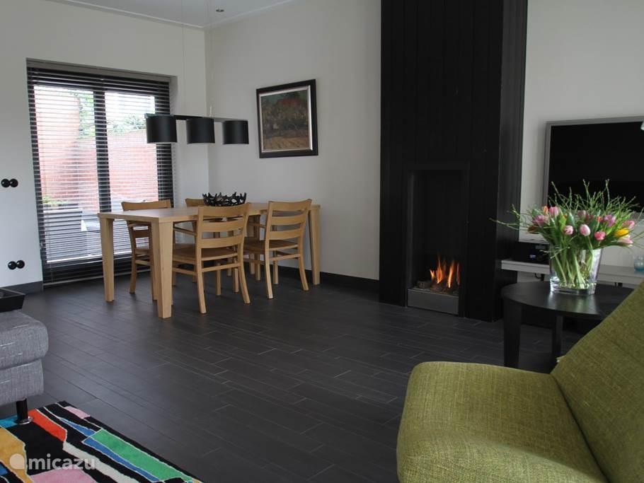 De woonkamer/eetkamer met sfeerhaard.