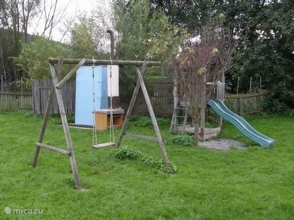 Schommel, speelhuisje en buitendouche